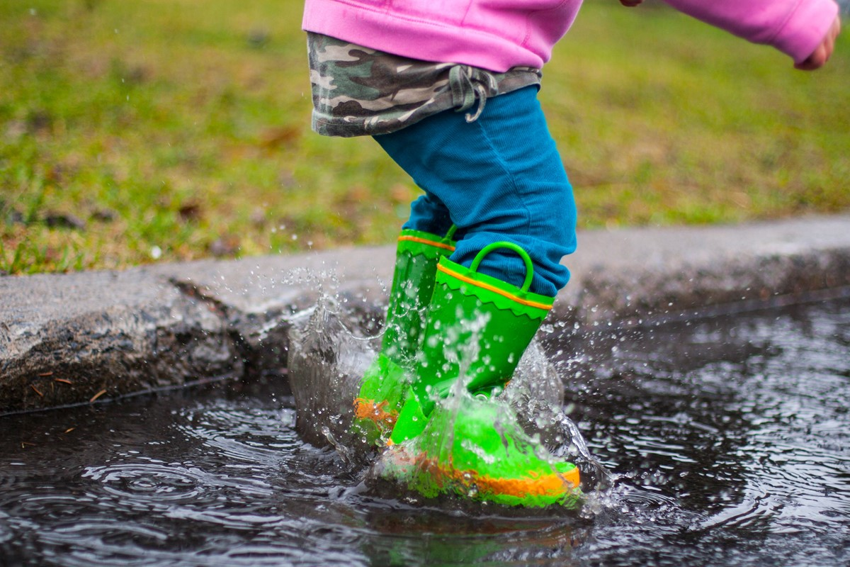 little girl jumping in puddle in wellies