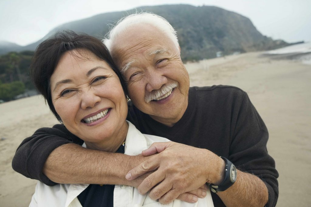 a-middle-aged-woman-and-man-on-the-beach-smiling-and-embracing-original-1024x681