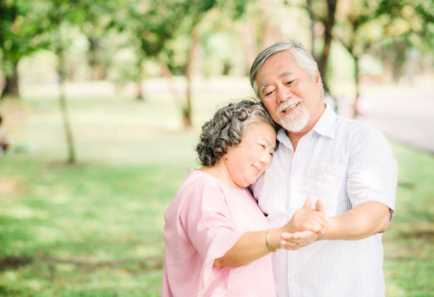 Happy senior Asian couple in love dancing in the park in sunny day